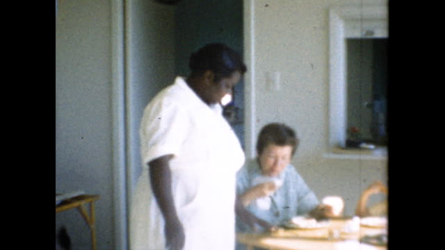 woman and child eating on the table; black woman cleans up table and smiles at camera - collaboratore domestico video stock e b–roll