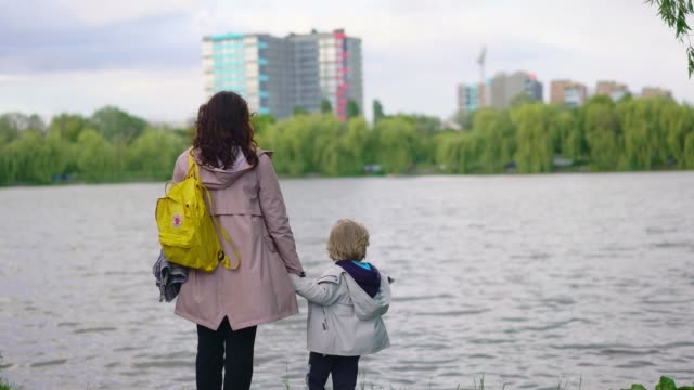 woman and child looking at lake in town - primary age child stock videos & royalty-free footage
