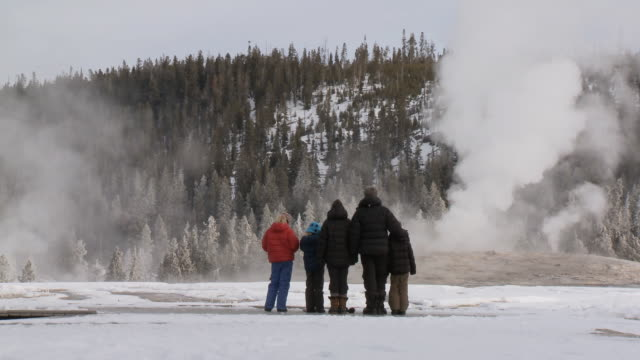 MS Woman and childs watching geyser erupting / Yellowstone National Park, Wyoming, United