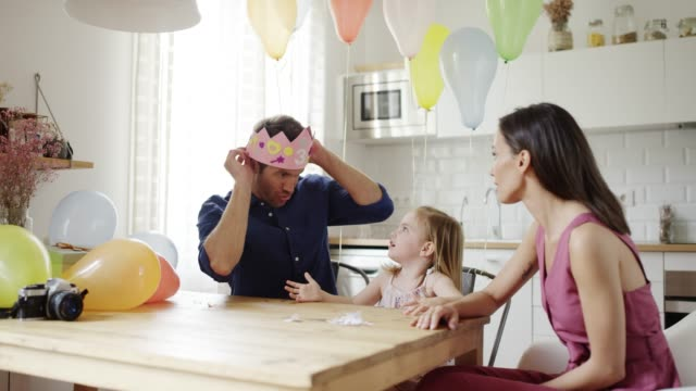 vídeos de stock e filmes b-roll de woman and daughter looking at man wearing crown - objeto decorativo