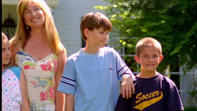 vídeos de stock e filmes b-roll de a woman and four children stand in front of a suburban home. - família com quatro filhos