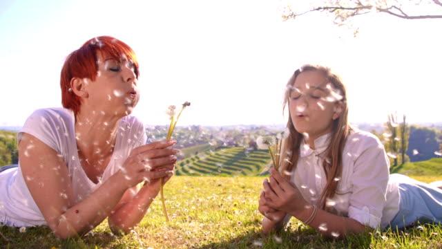 vídeos de stock, filmes e b-roll de slo mo mulher e menina soprando dentes de leão - soprando