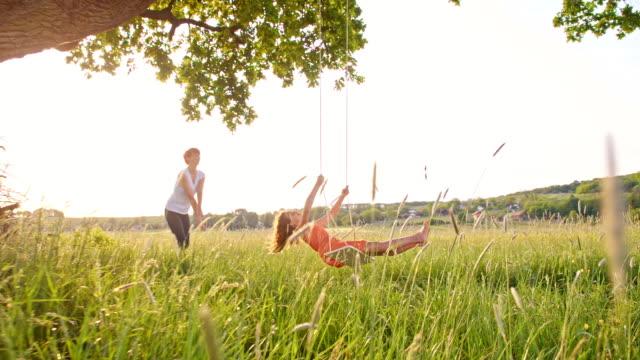vidéos et rushes de slo missouri femme et fille jouant sur balançoire sous un arbre - balançoire