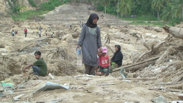 woman and her child walk across buried village from earthquake triggered landslide / audio - indonesia earthquake stock videos & royalty-free footage