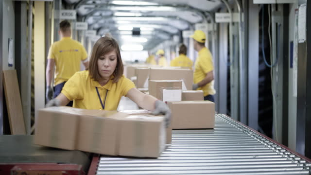 ds woman and her coworkers sorting packages on the conveyor belt - occupazione industriale video stock e b–roll