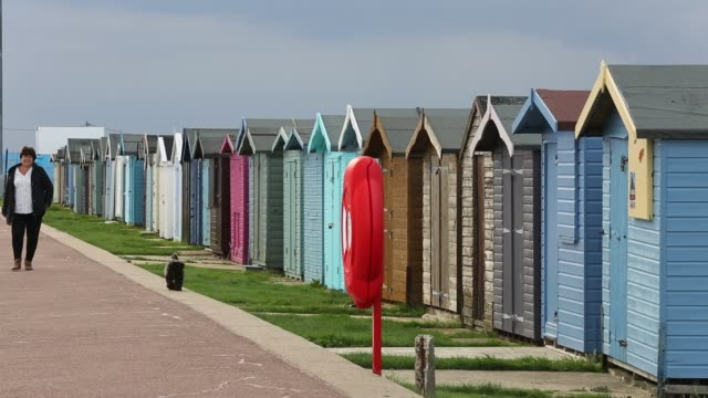 woman and her dog walk alongside a row of beach huts in brightlingsea, essex, united kingdom on september 3, 2015. - multi coloured stock videos & royalty-free footage