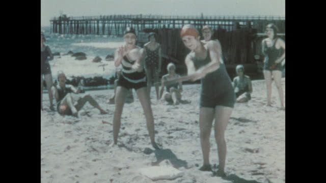 1930 a woman and her friends play softball on the beach - swimming cap stock videos and b-roll footage