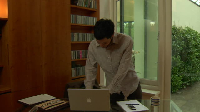 vídeos de stock e filmes b-roll de ws pan ms woman and her husband talking, then he walks into study, sits down at desk and uses laptop / london, england - sentar se