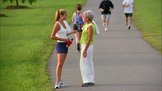 a woman and her mother  walk together on a pathway as joggers run by. - tochter stock-videos und b-roll-filmmaterial