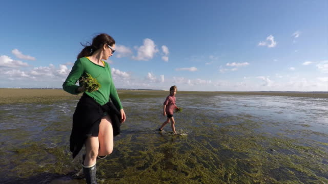 woman and her son walking on beach at low tide, Arcachon bay
