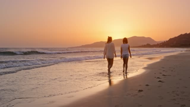 woman and her teenage daughter walking on the beach at sunset and talking - spain stock videos & royalty-free footage