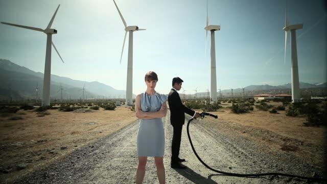 vidéos et rushes de woman and man at wind farm with gas pump - plan large