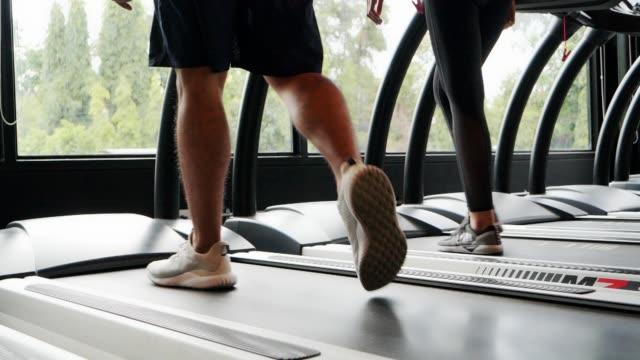 vídeos y material grabado en eventos de stock de mujer y hombre ateo caminando en la cinta de correr en fitness. concepto de estilo de ascensor salud, ejercicio, ciudad. imágenes a cámara lenta. - pedestrismo