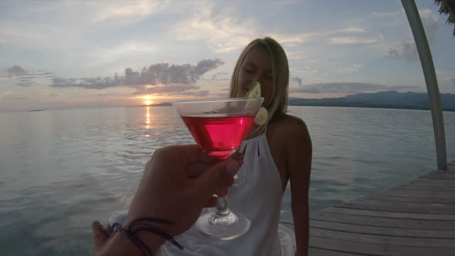 woman and man couple cheers toasting and having drinks on dock pier walkway at an island resort hotel. - slow motion - passion stock videos & royalty-free footage