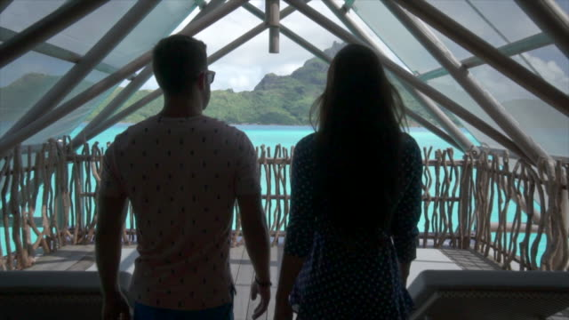 A woman and man couple walking to their overwater bungalow, lifestyle at a tropical island resort.