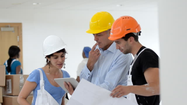 MS Woman and man decorators talking with man architect with tab / London, England, United Kingdom