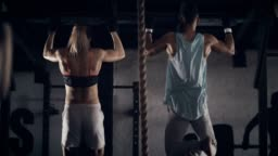 Woman and man doing chin-ups
