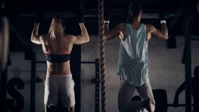 woman and man doing chin-ups - forza video stock e b–roll