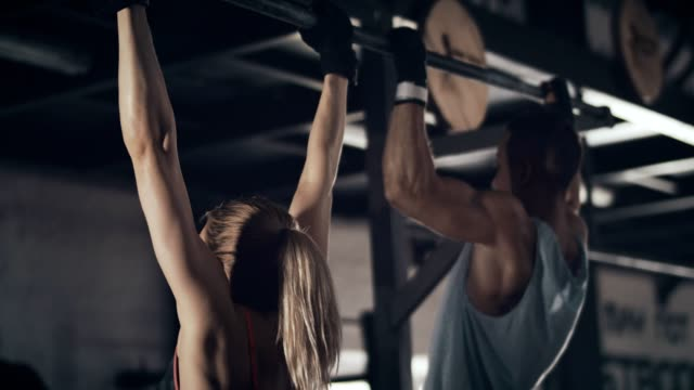 woman and man doing chin-ups - human muscle stock videos & royalty-free footage