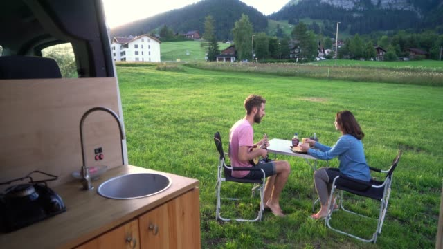 woman and man eating pancakes in camping near their camper van - camper van stock videos & royalty-free footage