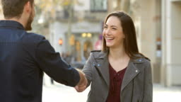 Woman and man handshaking in the street