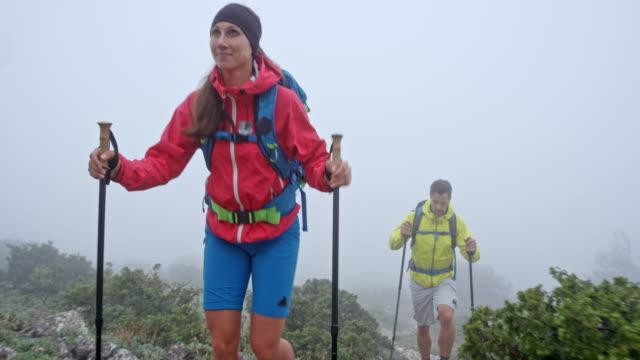 女と男の重い霧で山でのハイキング - ツレス点の映像素材/bロール