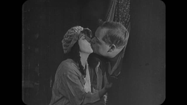 1916 woman (mabel normand) and man (fatty arbuckle) kiss longingly in their night clothes - 1916年点の映像素材/bロール