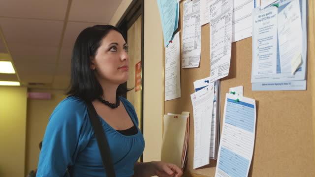 cu, pan, woman and man looking at job board in unemployment office, phoenix, arizona, usa - vetrinetta video stock e b–roll