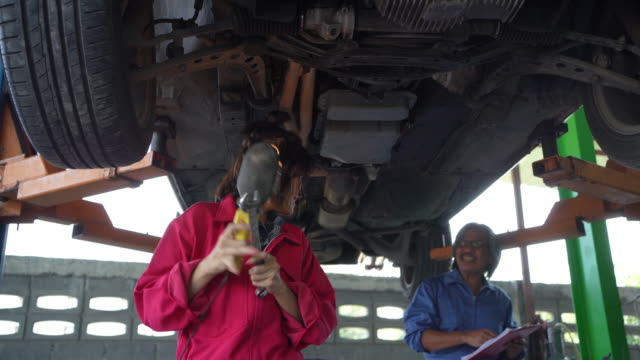 woman and man mechanic car repair worker in the auto repair. - sollevare video stock e b–roll