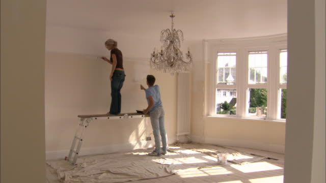 Woman and man painting wall / woman standing on work platform of multipurpose ladder
