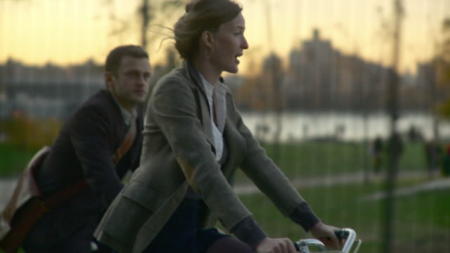 ms ts selective focus woman and man riding bicycles, city skyline in background / new york city, new york, usa - 單車 個影片檔及 b 捲影像