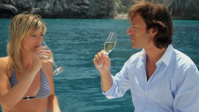ms woman and man sit on the stern of motorboat drinking champagne / golf de son termes, bunyola, mallorca, baleares, spain - champagne stock videos & royalty-free footage