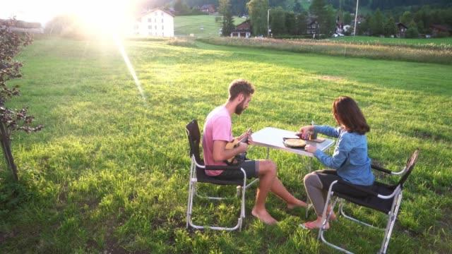 vídeos de stock, filmes e b-roll de mulher e homem que sentam-se na tabela no acampamento perto da camionete de campista - casal jovem