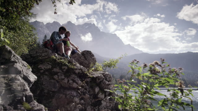 woman and man sitting on stone and drinking, mountain lake, dolly shot, , from the front, distance shot - distant stock videos & royalty-free footage