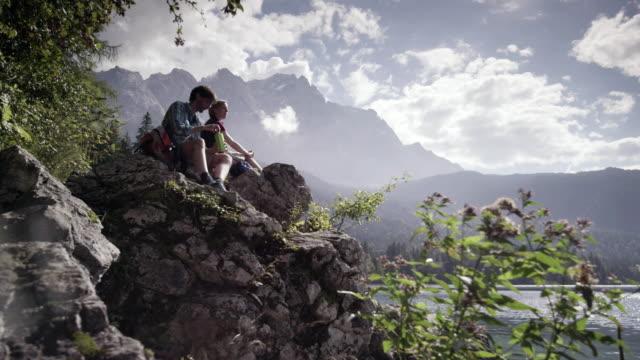 woman and man sitting on stone and drinking, mountain lake, dolly shot, , from the front, distance shot - avlägsen bildbanksvideor och videomaterial från bakom kulisserna