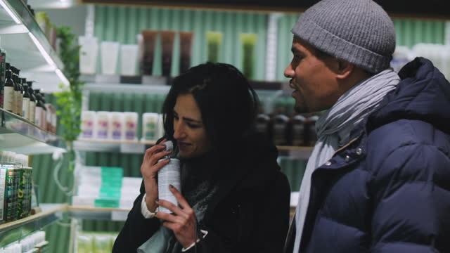 stockvideo's en b-roll-footage met woman and man smelling shampoo bottle in supermarket - winkeldisplay