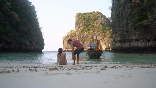 vídeos de stock e filmes b-roll de woman and man talking on the beach and looking at sea on koh phi phi island - ilhas phi phi