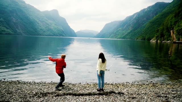 Vrouw en man gooien stenen in de fjord in Noorwegen