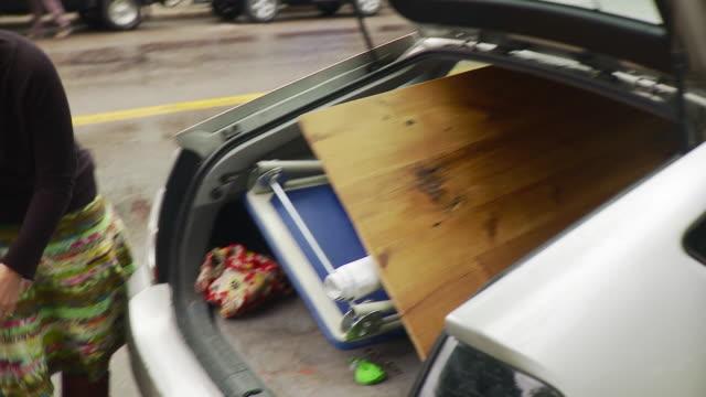 ms pan woman and man unloading car / burlington, vermont, usa  - burlington vermont stock videos & royalty-free footage