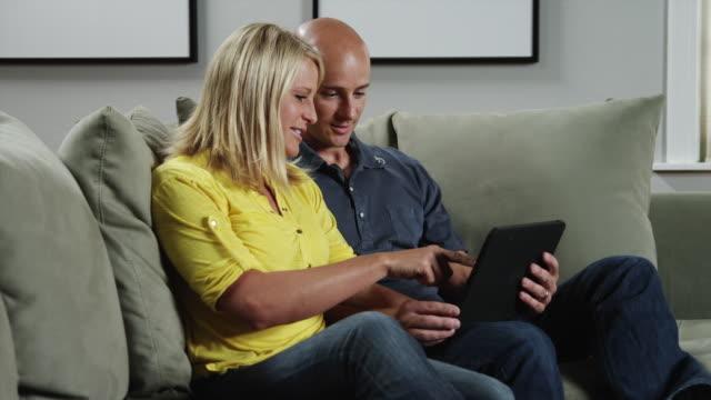 ms zi woman and man using digital tablet on sofa / orem, utah, usa - orem utah stock videos & royalty-free footage
