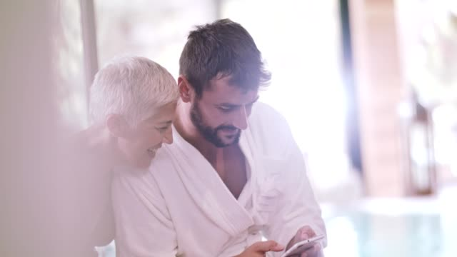 woman and man using mobile at spa - bathrobe stock videos & royalty-free footage