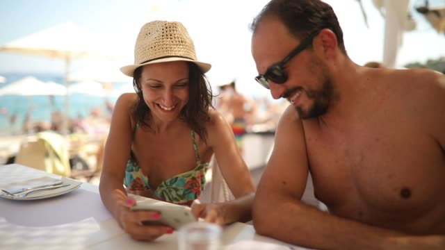 Woman and man using smart phone at the restaurant