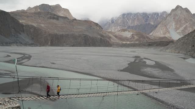woman and man  walking on suspension bridge in pakistan - suspension bridge stock videos & royalty-free footage