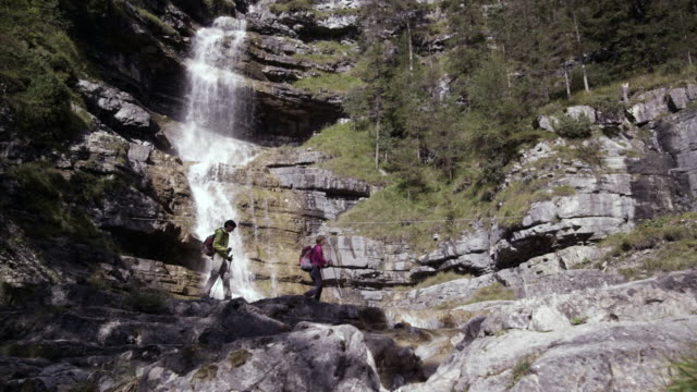 woman and man walking to waterfall, lateral, distance shot