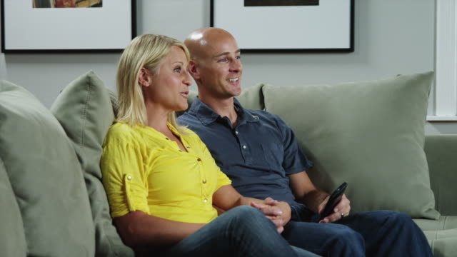 MS ZI Woman and man watching TV in living room / Orem, Utah, USA