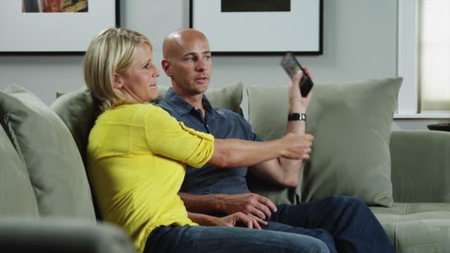 vídeos de stock, filmes e b-roll de ms ds woman and man watching tv in living room / orem, utah, usa - orem utah