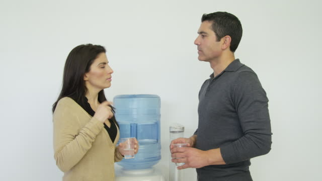 ms woman and mature man having discussion standing next to a water cooler - office politics stock videos & royalty-free footage