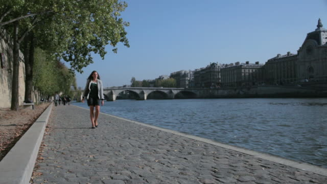 ws woman and others walking next the seine river / paris, france - pier stock videos & royalty-free footage