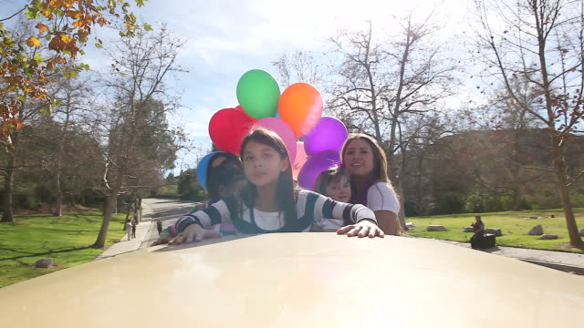 ms ts woman and small girls standing out of top of sunroof with balloons driving down at street / los angeles, california, united states  - sun roof stock videos & royalty-free footage