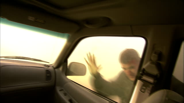 vídeos y material grabado en eventos de stock de a woman and teenage boy run toward a vehicle and climb in during a violent dust storm. - vendaval de polvo